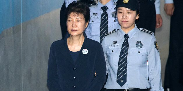 Park Geun-hye, former president of South Korea, left, is escorted by prison officers as she arrives at...