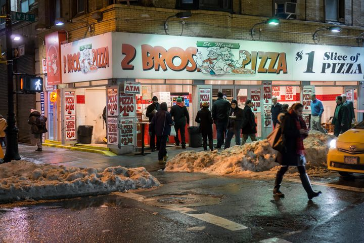 Pizza lovers line up at a 2 Bros. Pizza store in Midtown Manhattan.
