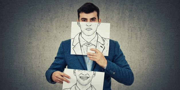 Businessman holding two white papers with different emotions drawn, one hiding half face with angry expressionon...