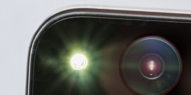 close up of the camera part of a smartphone during a picture with flash, the big flash creates a