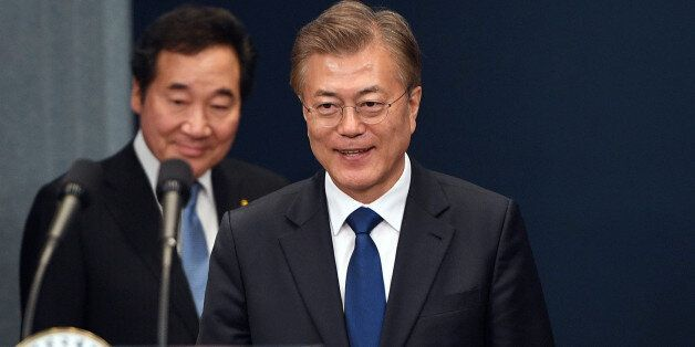 South Korea's new President Moon Jae-in (R) arrives to attend a press conference as Prime Minister nominee...