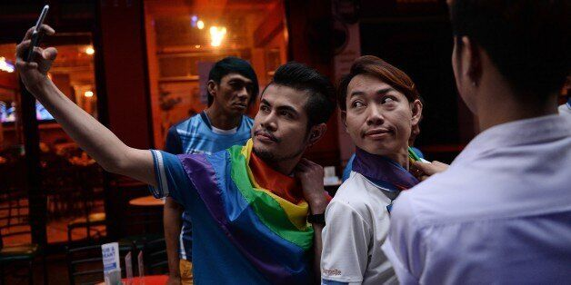 Members of the LGBT community in Thailand take photos as they gather in Bangkok on June 18, 2016 to take...