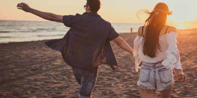Couple running free on the beach while holding