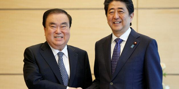 South Korean special presidential envoy Moon Hee-sang (L) shakes hands with Japan's Prime Minister Shinzo...