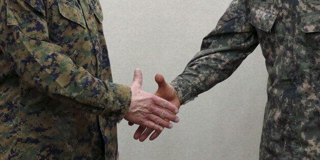 South Korean defense ministry's Director General Major General Jang Kyung-soo shakes hands with U.S....