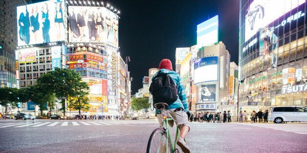 Young guy with backpack riding a bike on Shibuya crossing in Tokyo,