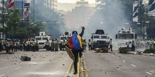 Riot police clash with demonstrators during a protest against the government of President Nicolas Maduro...