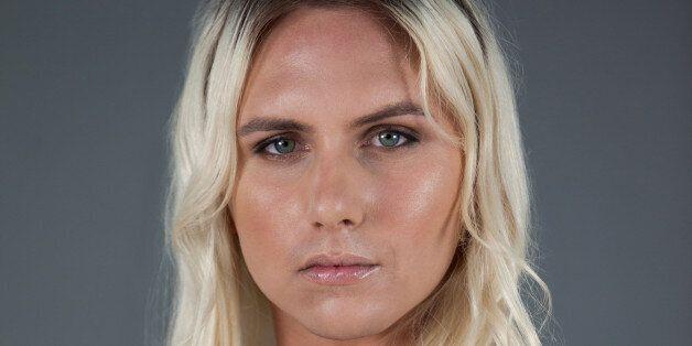 Portrait of transgender woman standing over gray