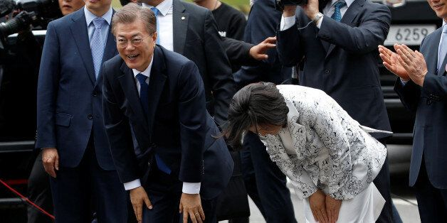 South Korea President Moon Jae-in and his wife Kim Jung-sook bow to greet to neighborhood residents as...