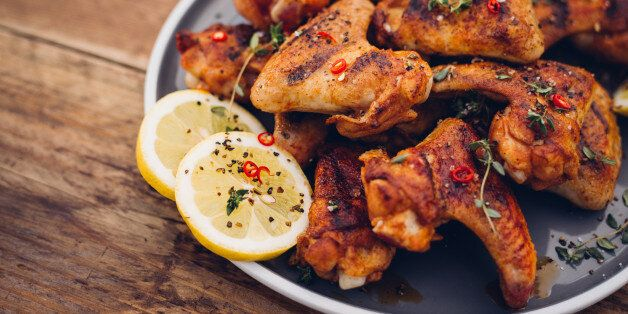 Spicy chicken wings sprinkled with chillie and herbs on a vintage wooden