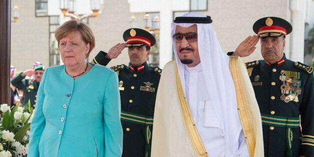 Saudi Arabia's King Salman bin Abdulaziz Al Saud stands next to German Chancellor Angela Merkel during...