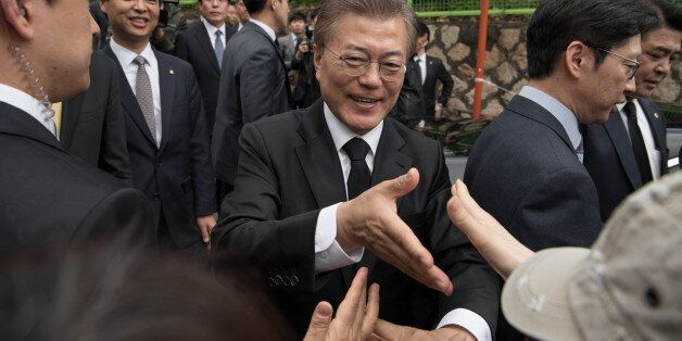 South Korean President Moon Jae-In greets supporters outside his home Seoul on May 10, 2017.Left-leaning...