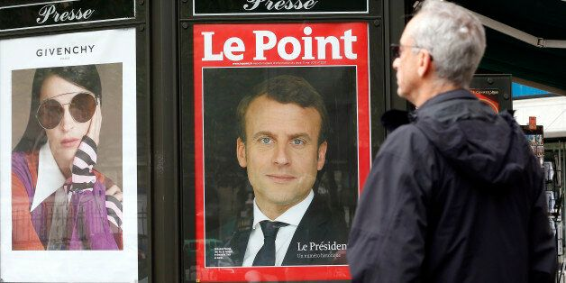 PARIS, FRANCE - MAY 08: A man walks past the poster of the French magazine front cover 'Le Point' with...