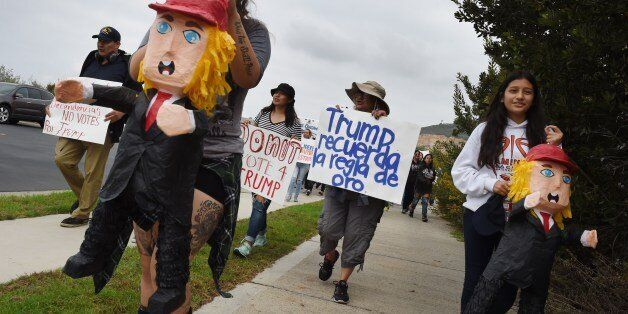 People carry Trump Pinatas during a protest rally denouncing alleged racist remarks by Republican presidential...