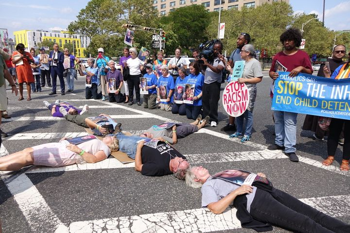 Catholic protesters form the shape of the cross and block a road outside Newark's Peter Rodino Federal Building, hoping to ra