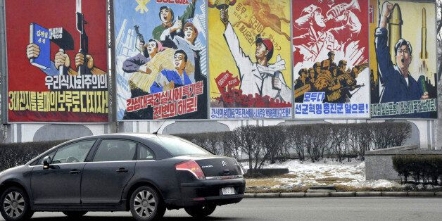 A car passes propaganda billboards hailing economic projects and the military along a roadway in Pyongyang...
