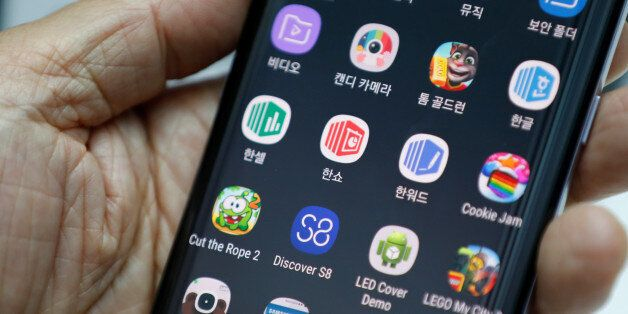 A man tries out a Samsung Electronics' Galaxy S8 smartphone at a shop in Seoul, South Korea, April 6,...