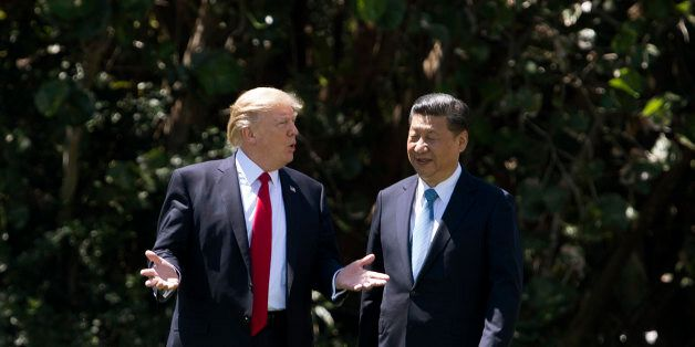 US President Donald Trump (L) and Chinese President Xi Jinping (R) walk together at the Mar-a-Lago estate...