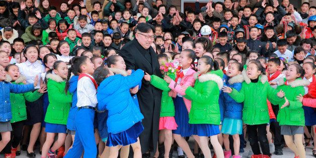 North Korean leader Kim Jong Un is hugged by children during his visit to Samjiyon County in this undated...