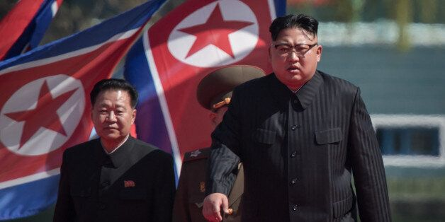 North Korean leader Kim Jong-Un (R) arrives flanked by vice-chairman of the State Affairs Commission...