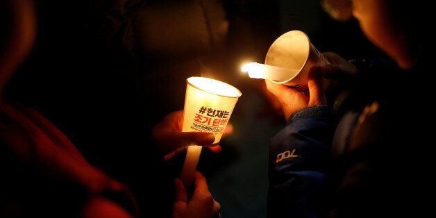 A child lights a candle during a protest demanding South Korean President Park Geun-hye's resignation...