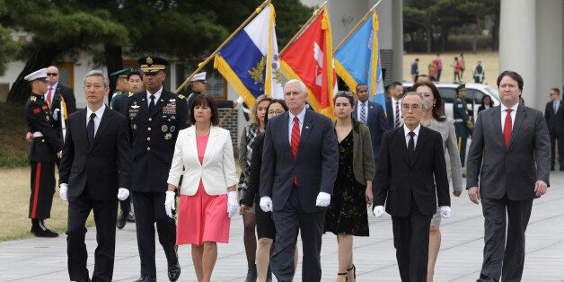 U.S. Vice President Mike Pence, center, and his wife Karen, center left, inspect hour guard upon their...