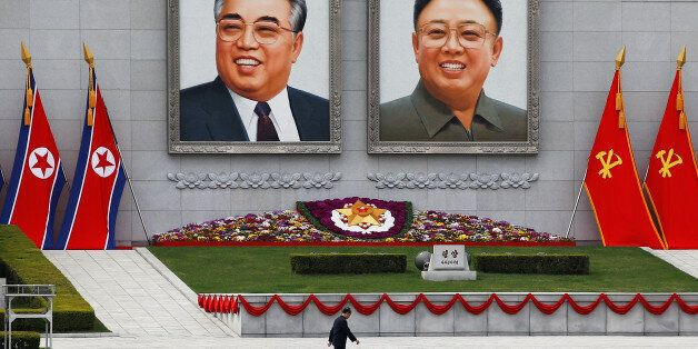 A man walks in front of portraits of North Korea founder Kim Il Sung and late leader Kim Jong Il in central...