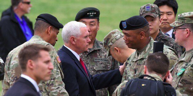 US Vice President Mike Pence (centre L) shakes hands with US military officers upon his arrival at army...