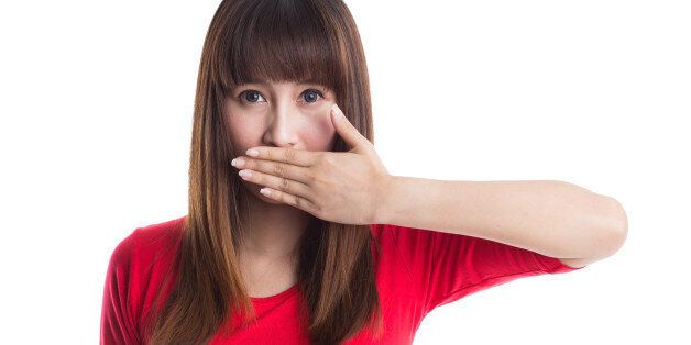 Beautiful young woman covering her mouth with her hand, isolated on white