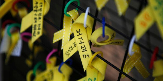 Yellow ribbons dedicated to the victims of the Sewol ferry disaster are seen hung on a fence in central...