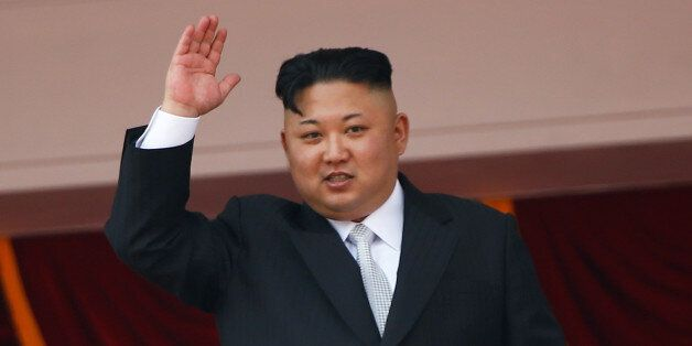 North Korean leader Kim Jong Un waves to people attending a military parade marking the 105th birth anniversary...