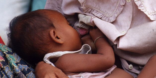 SIEM REAP, CAMBODIA - 2003/08/01: Chan Heit, 24, nurses her baby, Sey Lek who is less than a year old,...