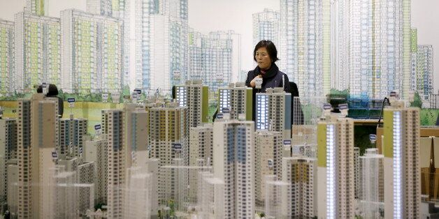 A visitor looks at a miniature model of an apartment complex which is currently under construction at...