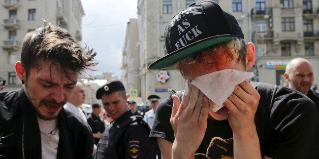 Gay rights activists react after being pepper sprayed by anti-gay protesters during an LGBT (lesbian,...
