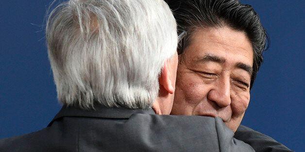 EU Commission President Jean-Claude Juncker (L) embraces Japan's Prime Minister Shinzo Abe before an...