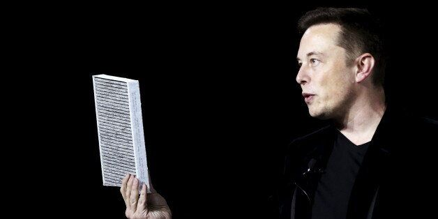 Tesla Motors CEO Elon Musk holds a car air filter during a presentation of the Model X electric sports-utility...