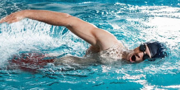 Young man swimming the front crawl in a