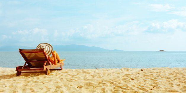 woman sunbathing in beach chair with outstretched arms on the