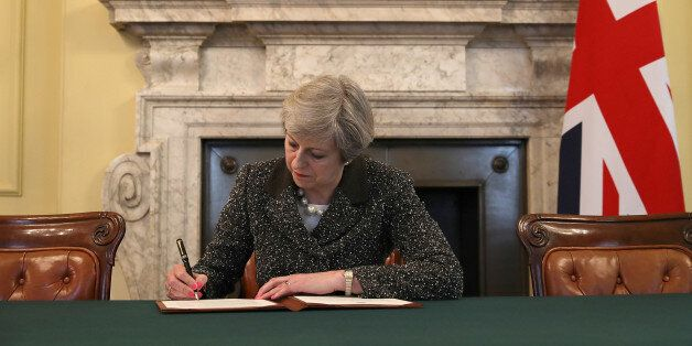 British Prime Minister Theresa May in the cabinet office signs the official letter to European Council...