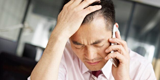 asian businessman talking on cellphone looking sad and