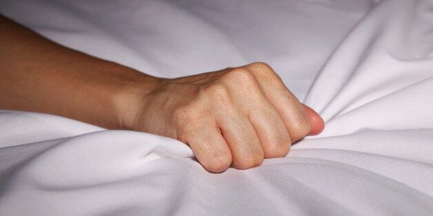 Woman's hand grabbing bed sheets during an