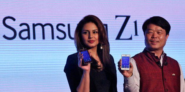 Hyun Chil Hong (R), president and chief executive of Samsung India Electronics, and Bollywood actress...