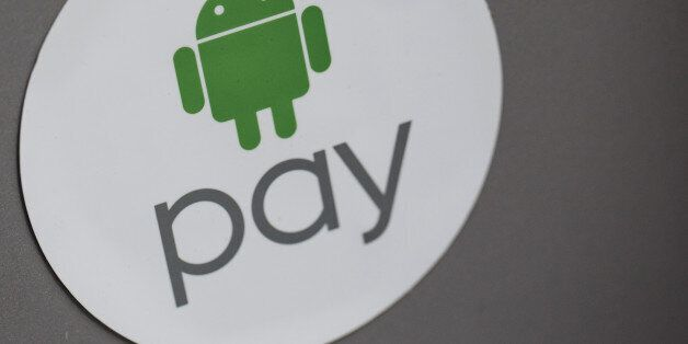 Signage for Google Inc.'s Android Pay is displayed outside a store in Hong Kong, China, on Tuesday, Nov....