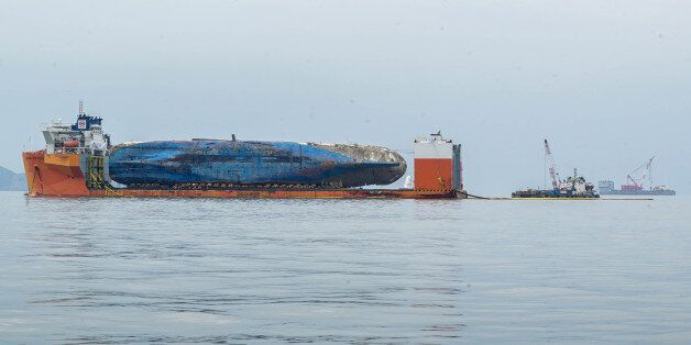 The sunken ferry Sewol is seen on a semi-submersible transport vessel during the salvage operation in...