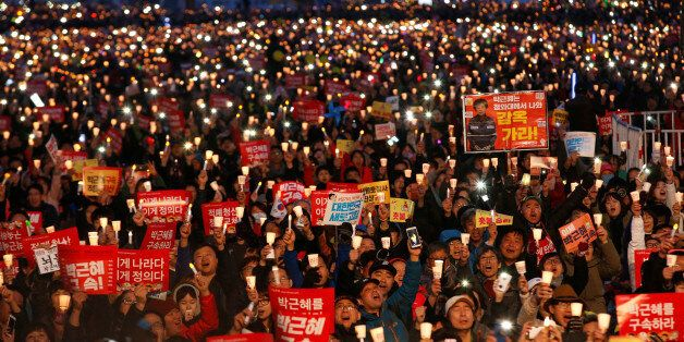 Protesters hold candles as they celebrate the impeachment of South Korea's ousted leader Park Geun-hye...