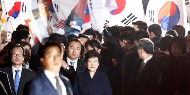 South Korea's ousted leader Park Geun-hye greets her supporters as she arrives at her private home in...