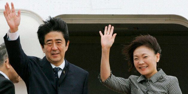 Japan's Prime Minister Shinzo Abe (L) and his wife Akie wave before boarding an aircraft as they depart...