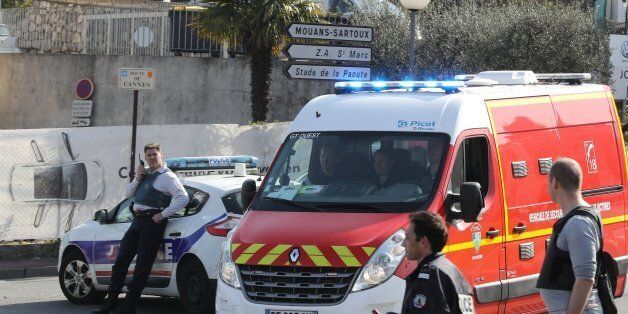 Policemen stand near a police and a firefighter vehicle in the southern French town of Grasse, on March...