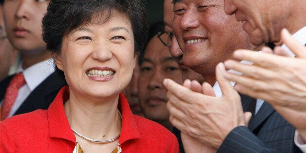 FILE PHOTO: Lawmakers and supporters of Park Geun-hye (L) clap their hands at the main office of the...