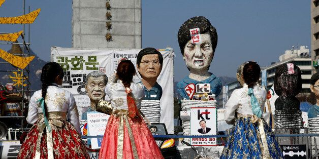 Tourists wearing traditional costume 'Hanbok' take picture of a statue depicting South Korea's ousted...